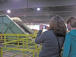 Two people taking a photo of a sorter at the recycling center