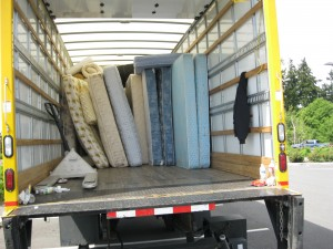 A lot of mattresses in the back of a cargo truck ready for recycling