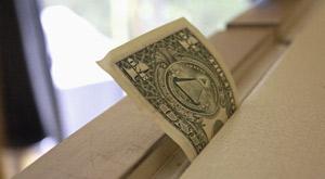 Dollar bill test- a dollar bill sticking out of a refrigerater