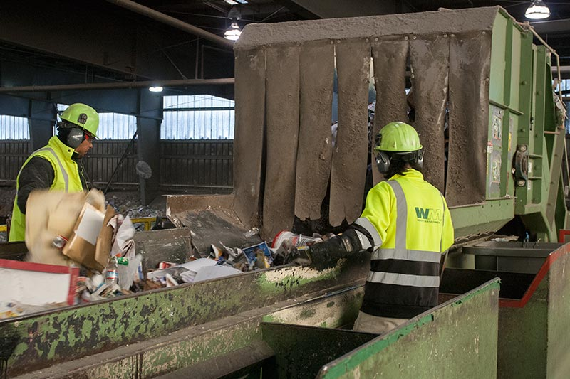 Workers picking contaminants off conveyor line at Cascade Recycling Center.