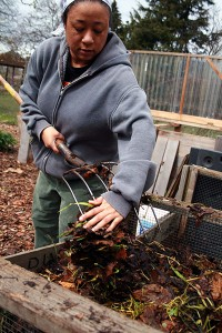 woman turning a backyard compost pile with a pitchfork