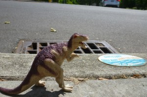 Dinosaur hanging out by a storm drain