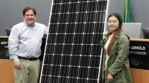 Deputy Mayor Jay Arnold with student and solar panel for City Hall